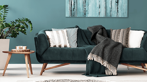 Dark green sofa with cushions and throws
