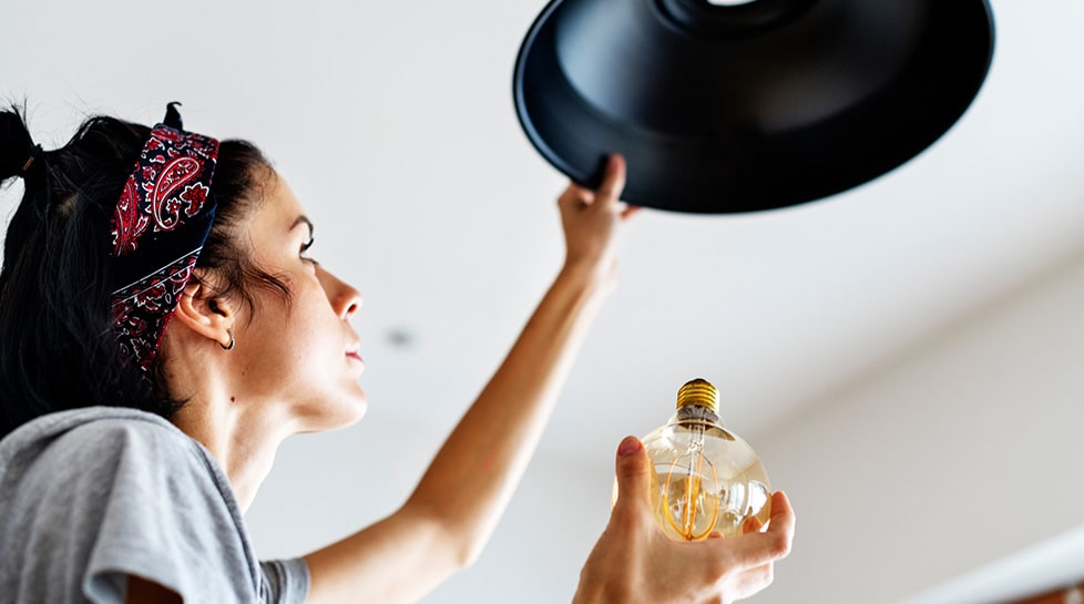Young woman changing lightbulb in home for February DIY