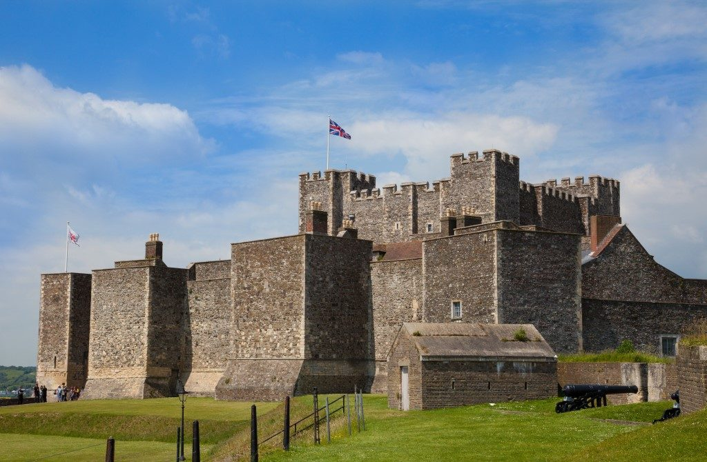 Picture taken of old English Heritage Dover Castle in Kent with flag raised and clouds in the blue sky