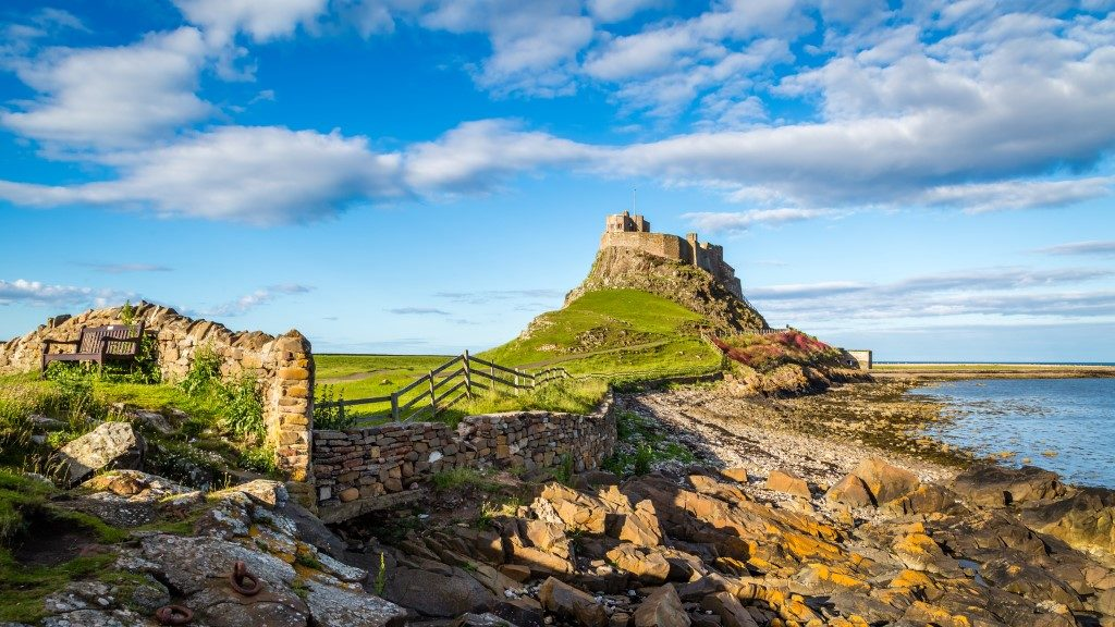 Picture taken of the holy island of Lindisfarne with rocks and the ocean nearby.