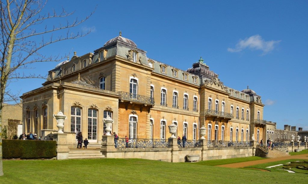 Picture taken of old English Heritage site hall in Wrest Park on bright sunny day with blue sky and green grass