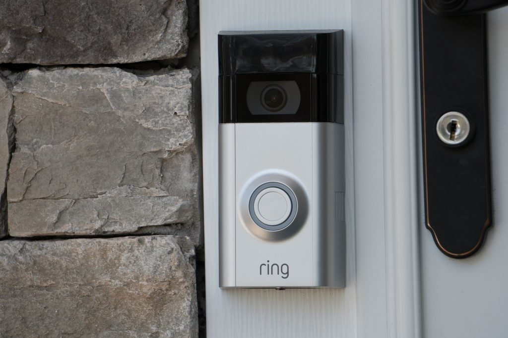 picture of ring smart doorbell with camera next to stone wall