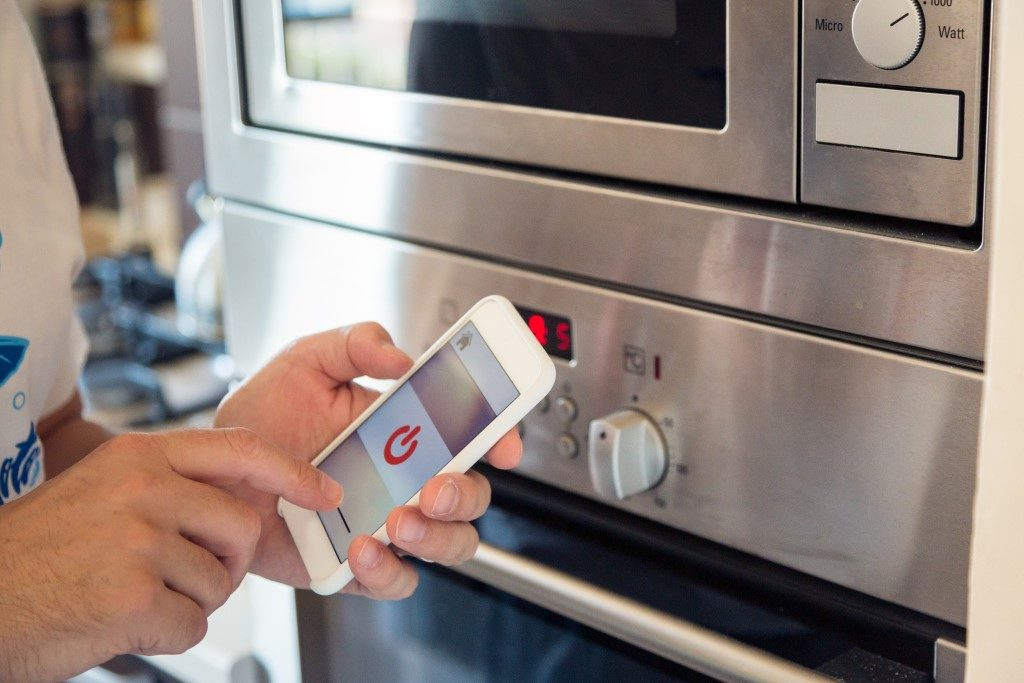 picture of smart oven being activated through mobile phone app