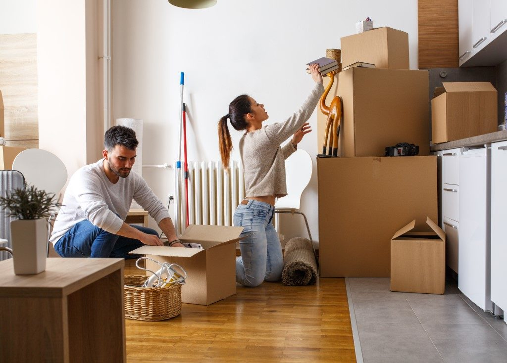 Image of young couple decluttering and organising their items into cardboard boxes