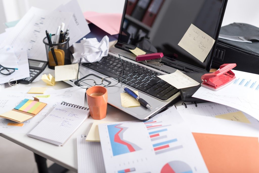 Image of messy desk with laptop covered in clutter, paper and mess